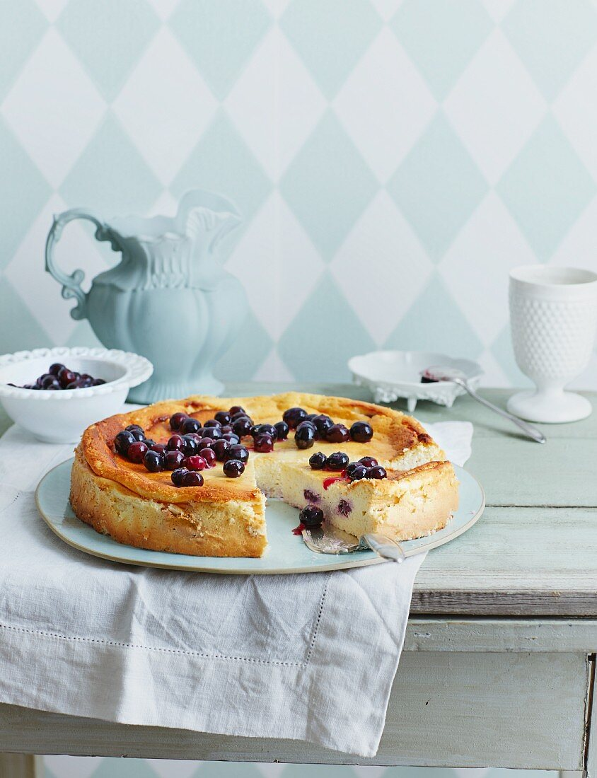 Slice of Blueberry Cheesecake on a Plate, Whole Cheesecake with Slice Removed