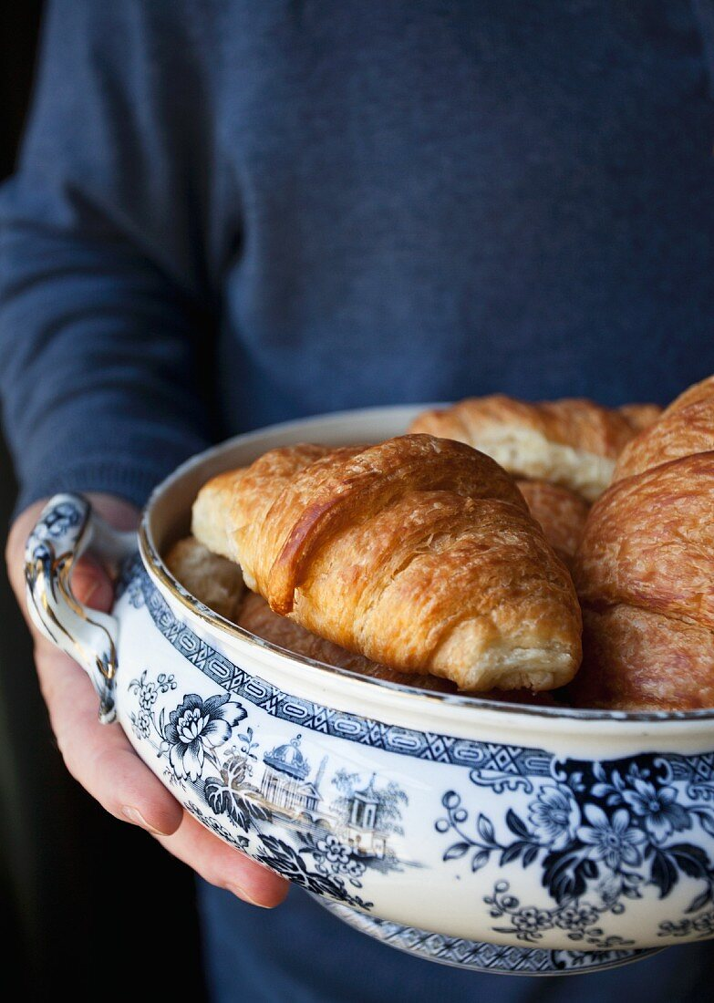 A man holding an antique bowl of croissants