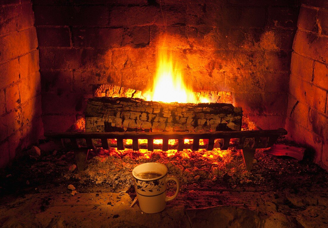 A mug of tea in front of a fireplace