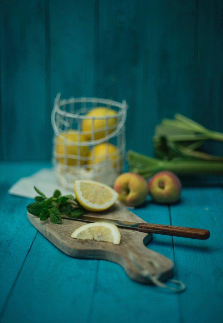 An arrangement of lemons, peaches, mint and rhubarb
