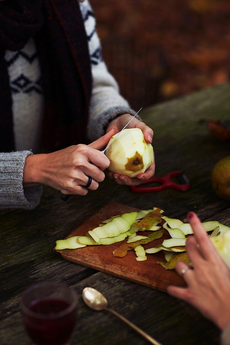 A woman peeling a pear