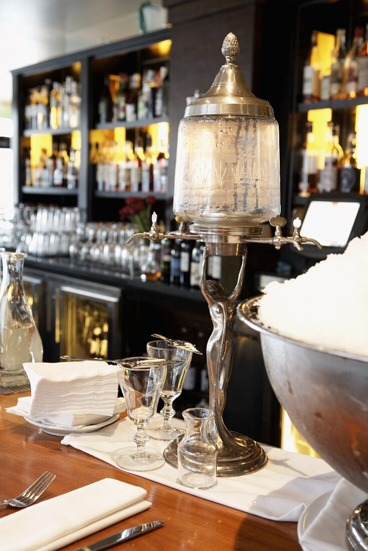 An art deco style table lamp and ice buckets behind the bar in a restaurant in front of rows of spirits and glasses