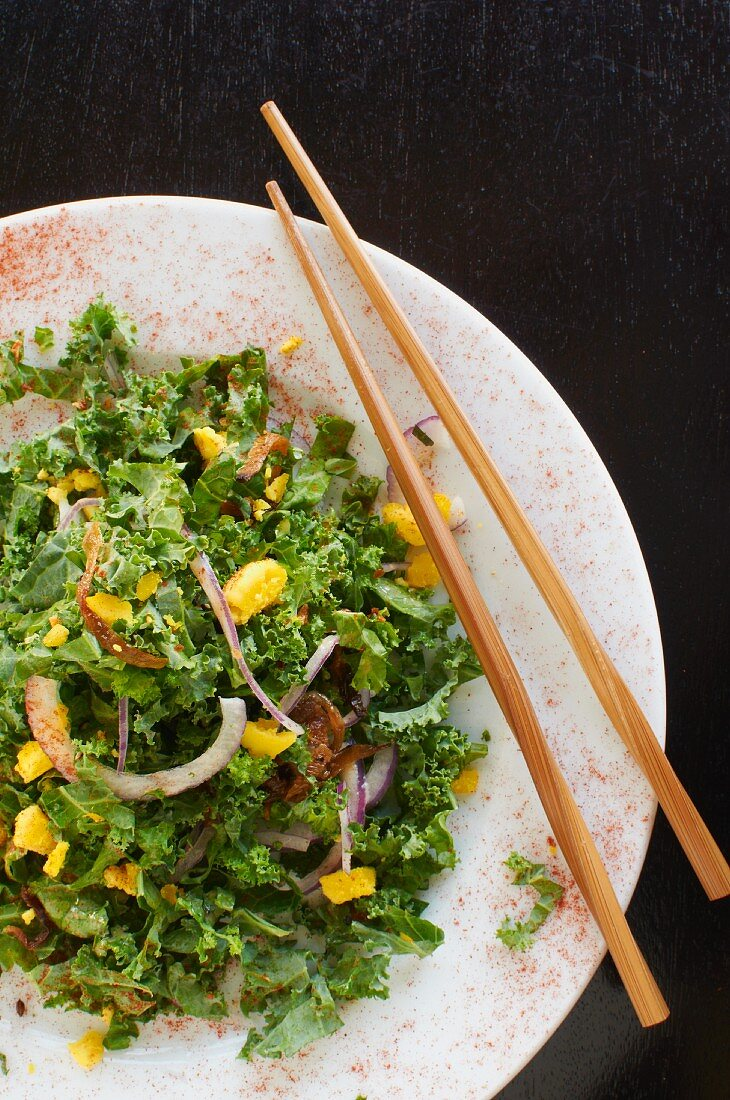 Chopped kale salad with hard-boiled egg crumbs, red onions, bacon bits and citrus vinaigrette
