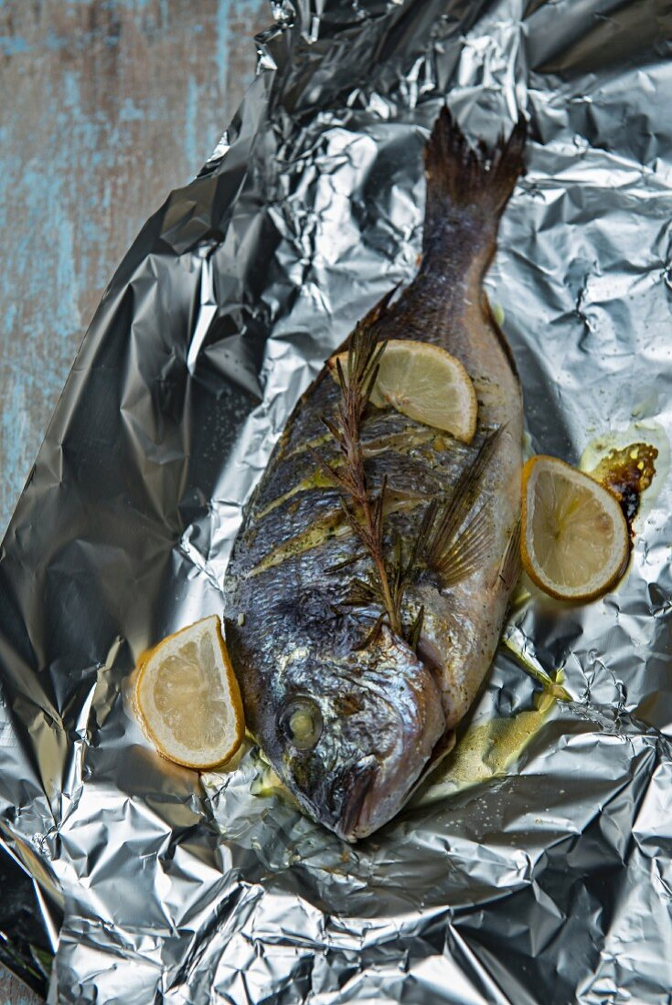 Seabream roasted in aluminium foil with lemons and rosemary