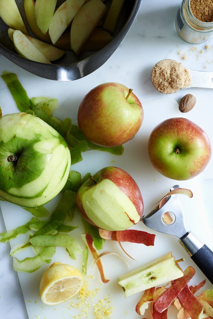 Peeled apples and ingredients for apple pie