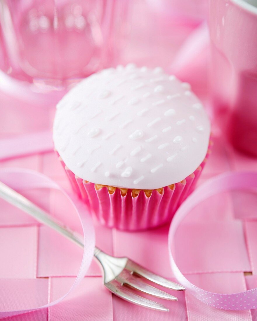 A cupcake with white fondant glaze