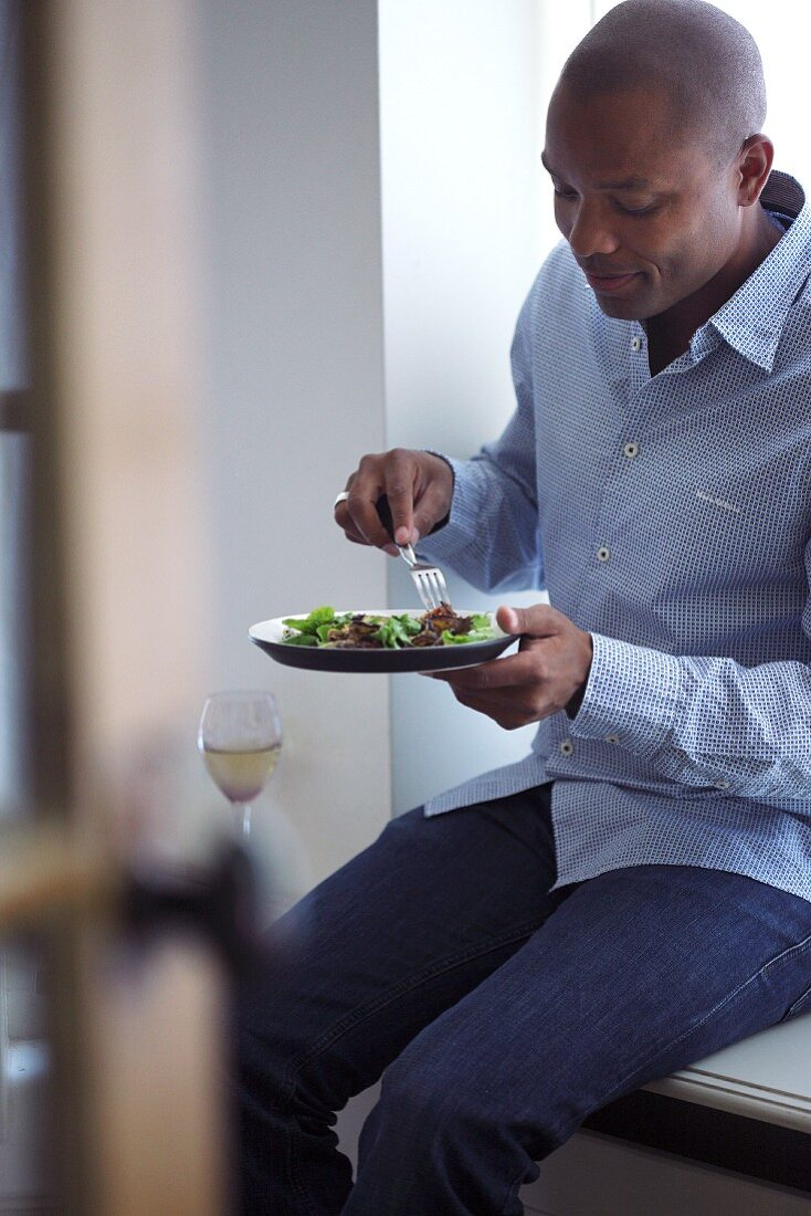 A man eating with a glass of wine on a window sill