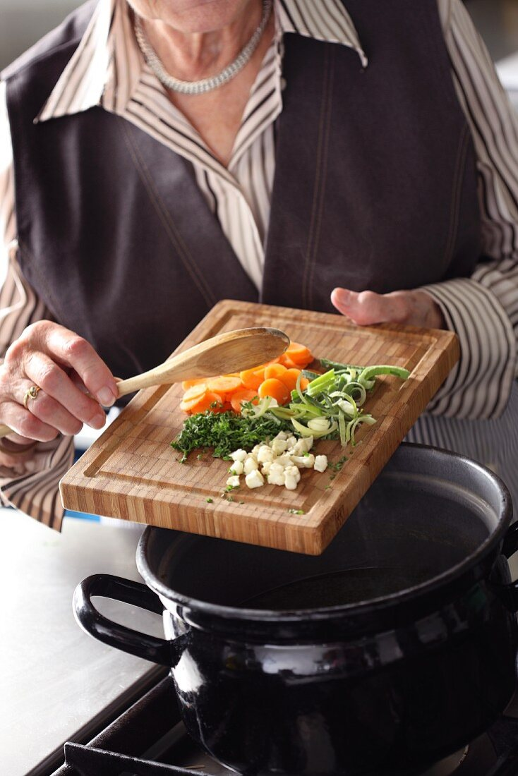 Chopped vegetables being added to a pot