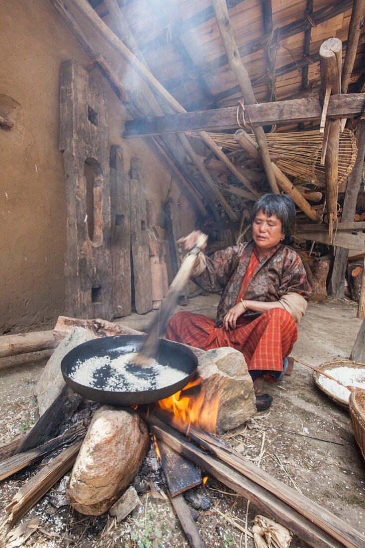 Frau aus Thimphu in traditioneller Kleidung bei der Reiszubereitung in einem einfachen Holzhaus, Bhutan
