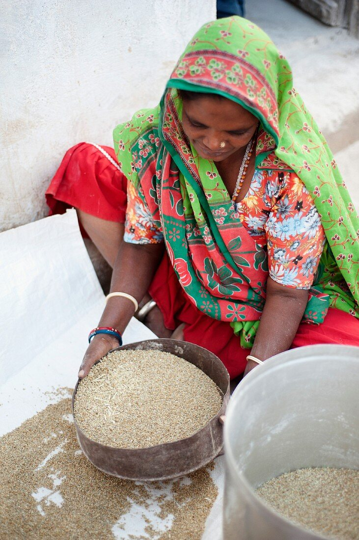 A young woman sifting millet, Nirona, Kachchh, Gujarat, India