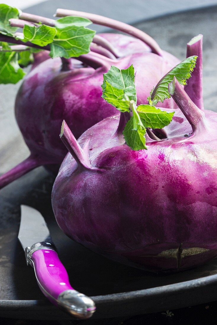 Two purple kohlrabi with leaves in a black bowl with a purple kitchen knife