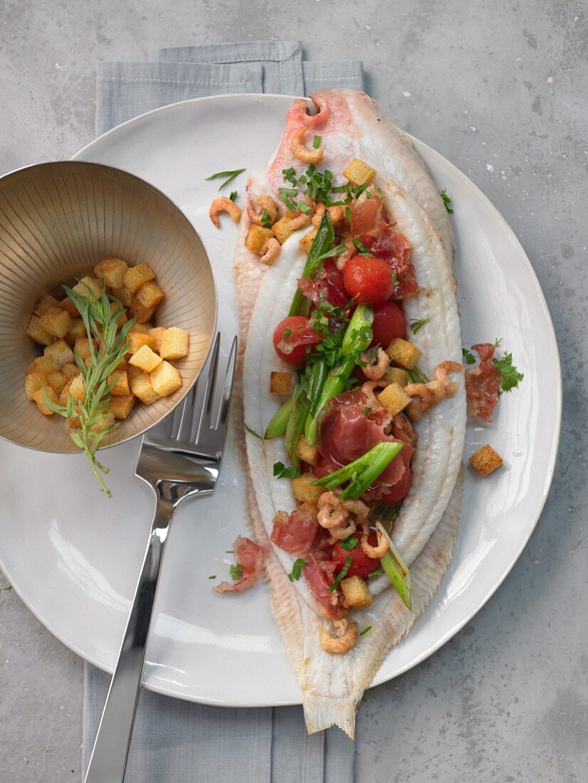 Stuffed oven-roasted sole with croutons, shrimps, cherry tomatoes and herbs