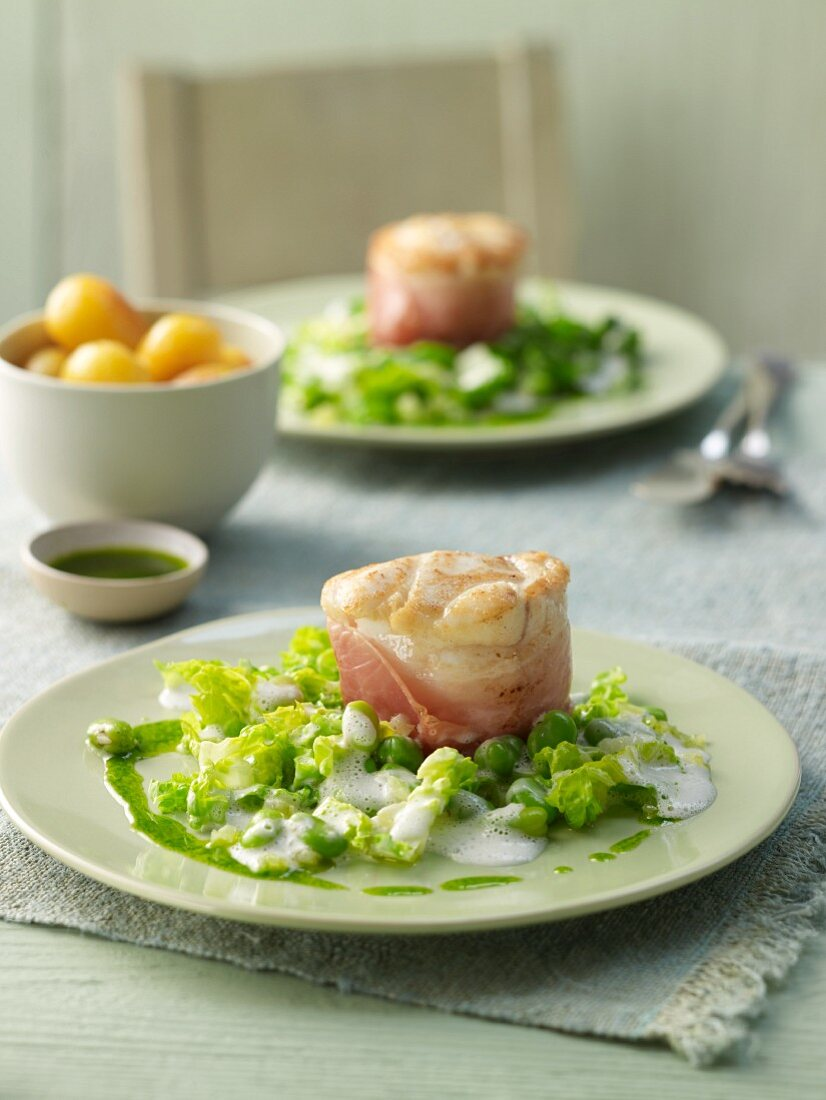 Monk fish tournedos in bacon with basil oil on green bean seeds and lettuce strips