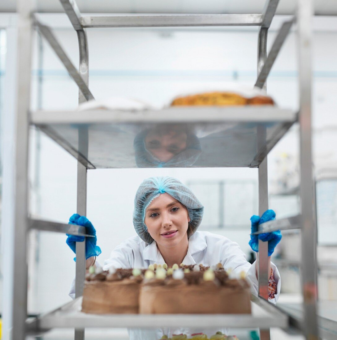 A baker pushing a trolley of freshly baked cakes in a cake factory