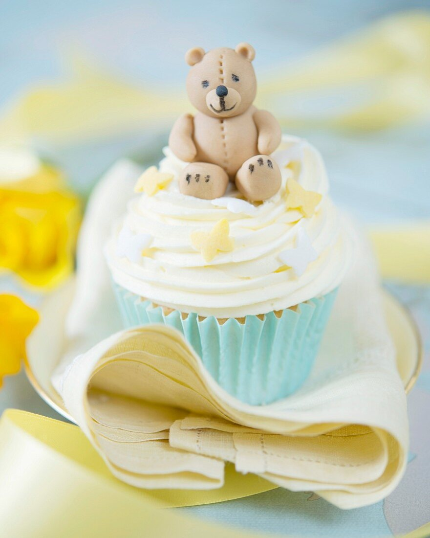 A cupcake decorated with a fondant teddy bear