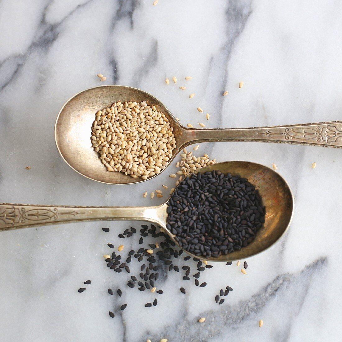 Light and dark sesame seeds on silver spoons (close-up)