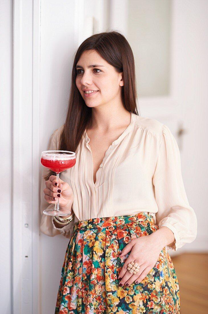 A woman holding a glass of virgin grapefruit margarita