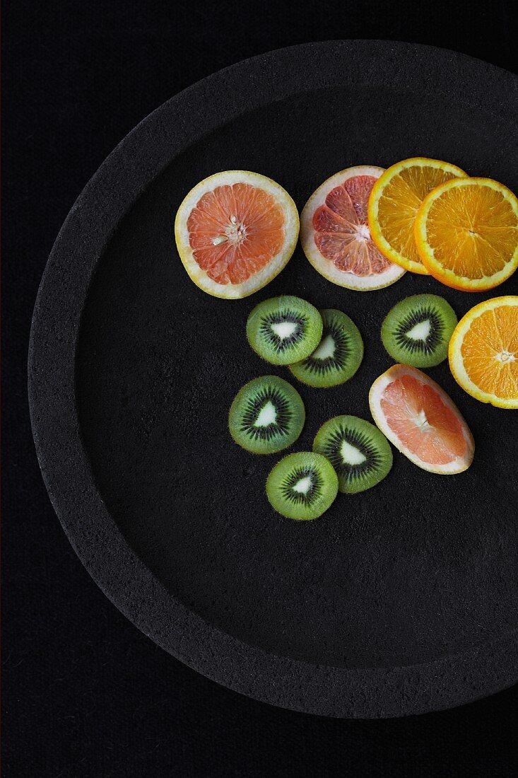 Grapefruit, orange and kiwi slices on a black plate