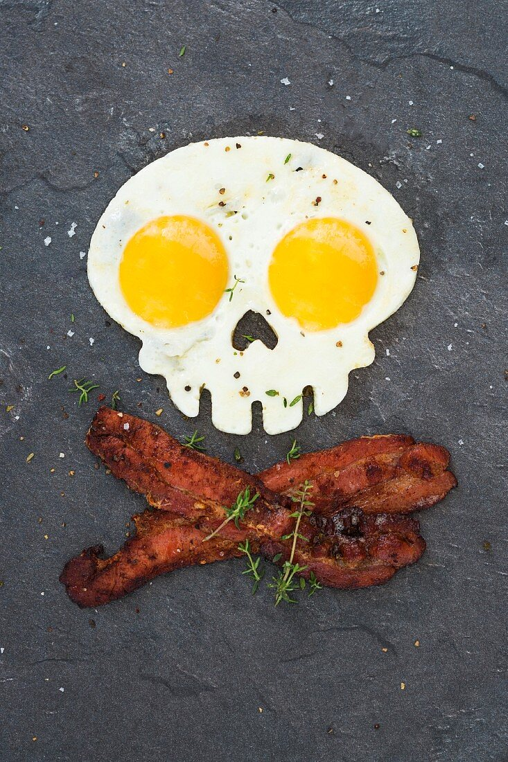 A skull-shaped fried egg with crispy bacon on a slate platter