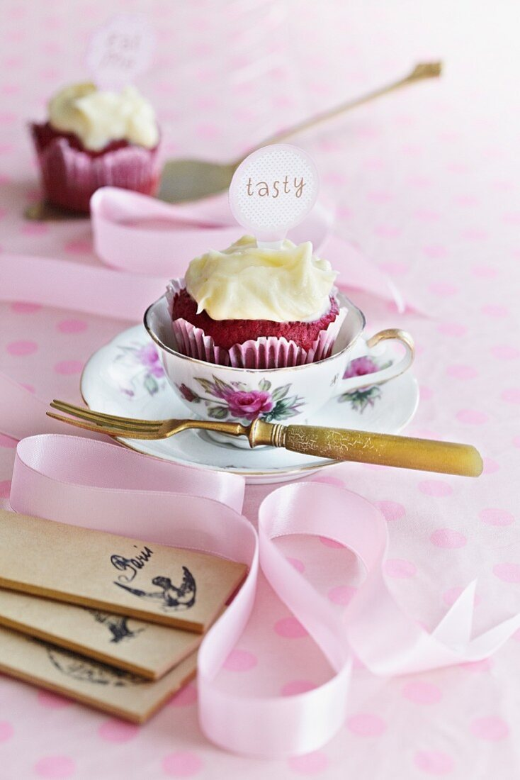 A berry cupcake with frosting and a label served with a cup of coffee