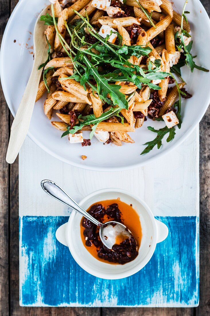 Summer pasta salad with dried tomatoes, feta cheese and rocket