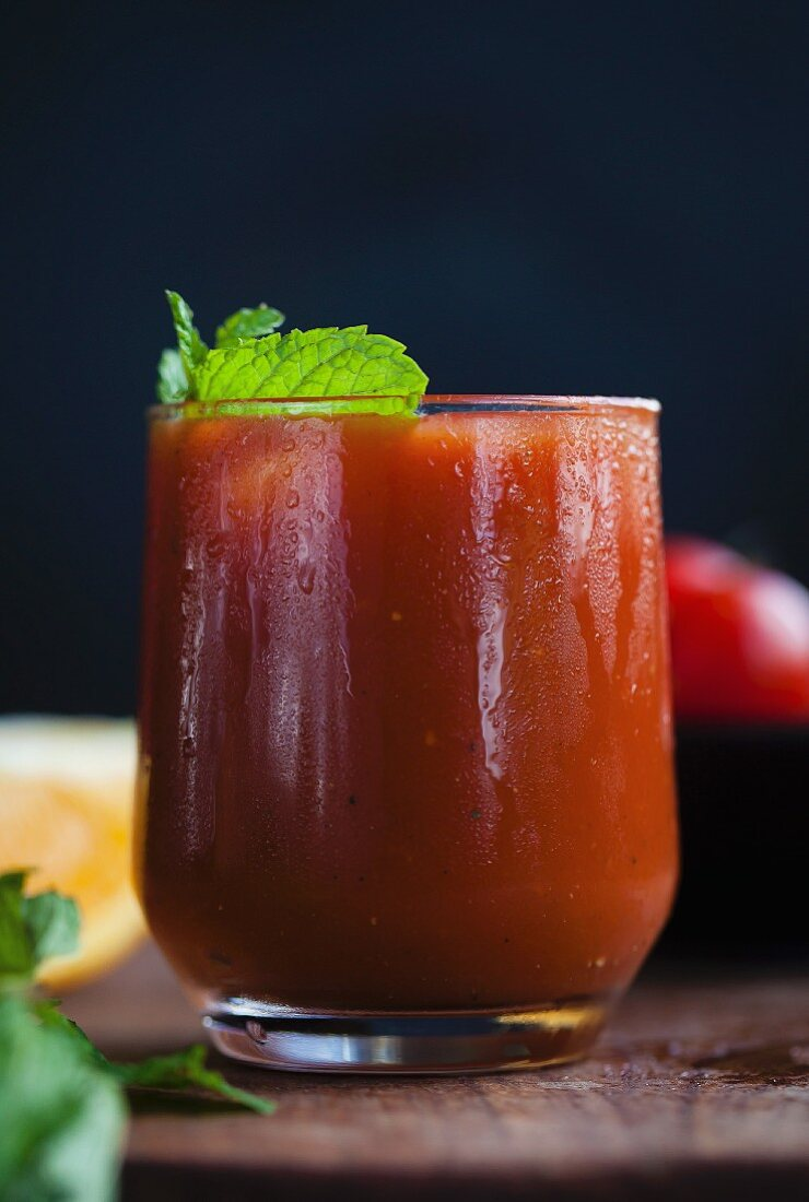 A glass of tomato and orange juice with fresh mint