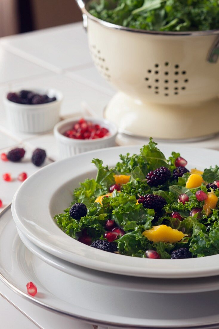 Kale salad with mulberries, pomegranate seeds and mango dressing