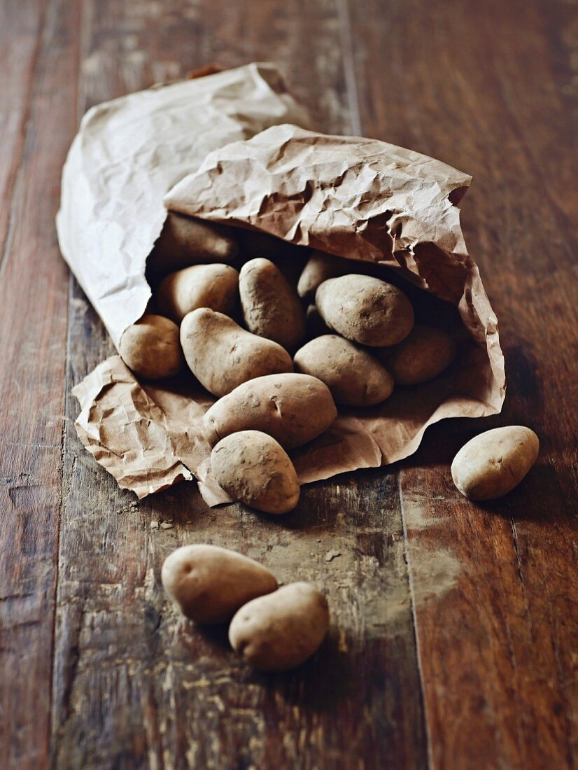 Potatoes in a paper sack on a wooden surface