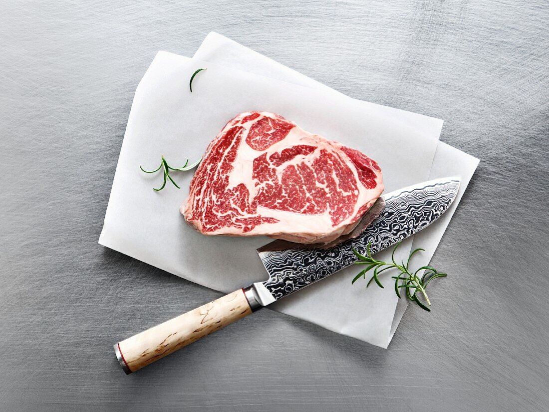 Wagyu ribeye steak with rosemary and a knife on a piece of parchment paper
