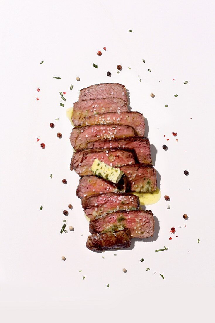 Sliced medium beefsteak with herb butter and spices