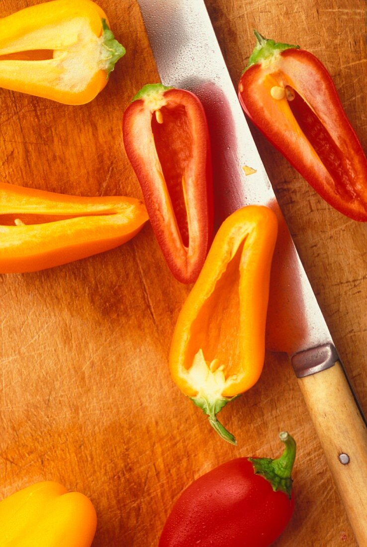 Mini red and yellow peppers on a chopping board with a knife