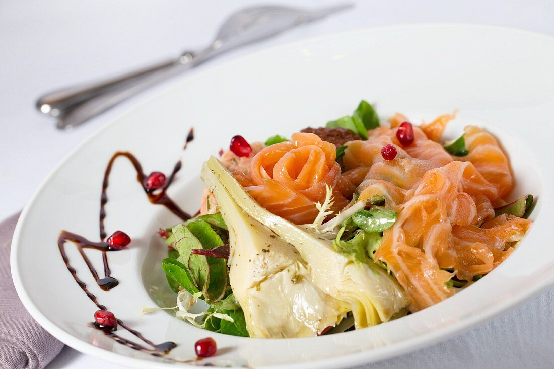A mixed leaf salad with artichokes, smoked salmon and pomegranate seeds