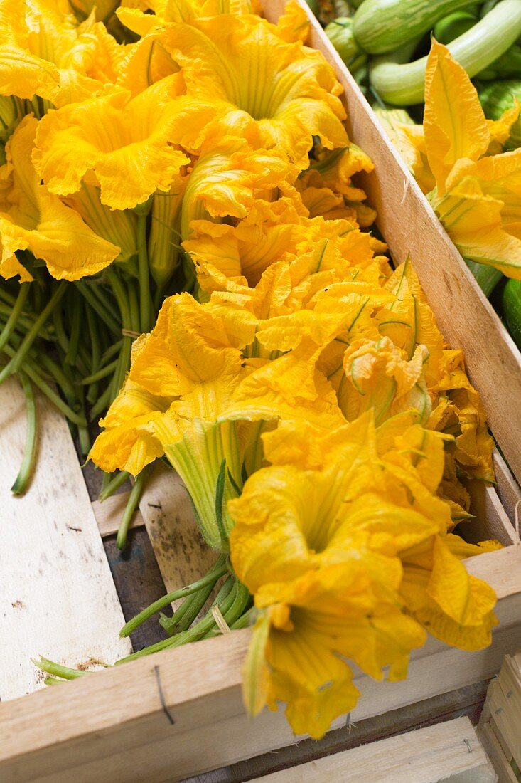 Courgette flowers in a wooden crate at a weekly market on Corsica