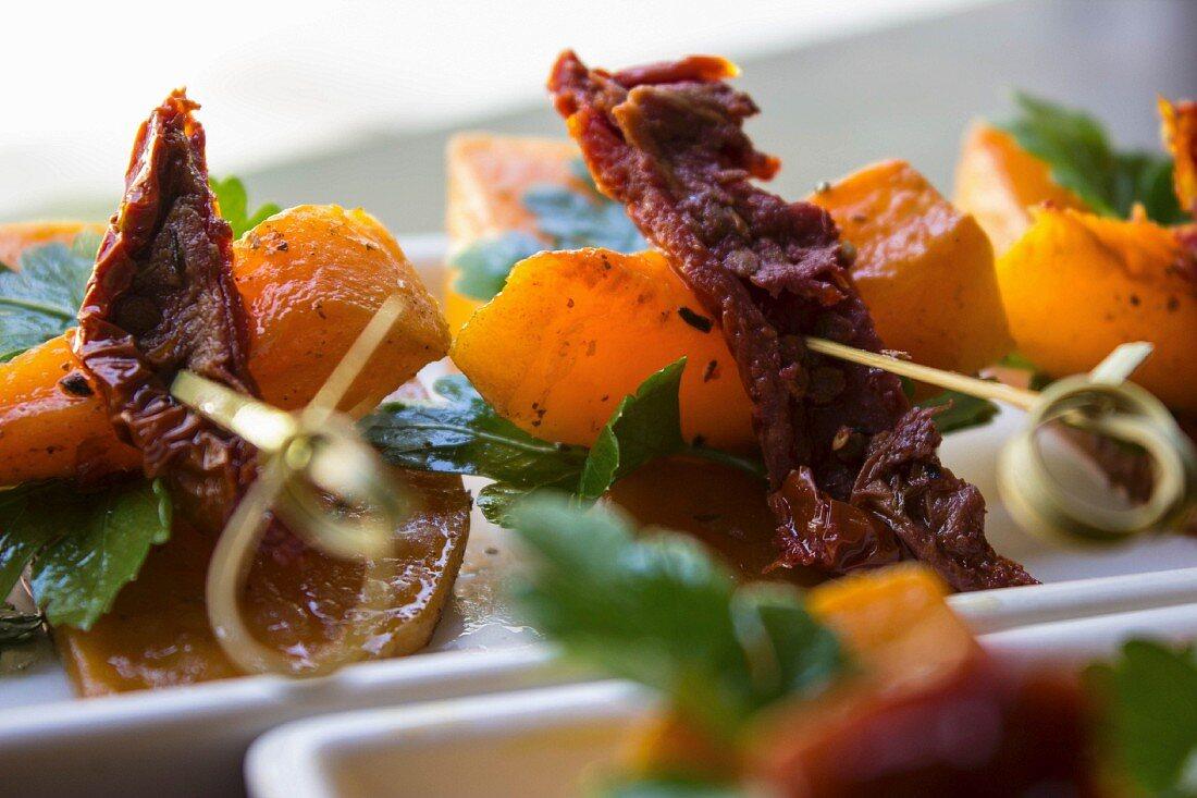 Hokkaido pumpkin skewers with dried tomatoes, Szechuan peppers and parsley on sweet potatoes