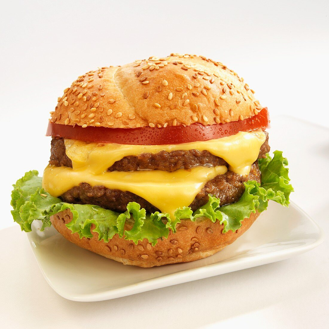 A double cheese burger with tomatoes on sesame seeds bun