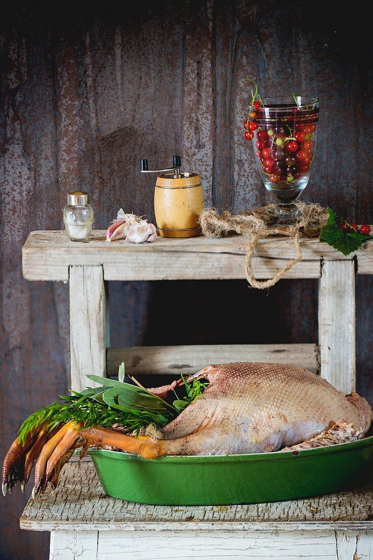 A ready-to-roast goose with a herb stuffing in a green roasting dish on a rustic wooden table