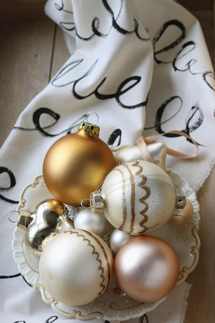 Christmas baubles in vintage bowl on hand-painted fabric