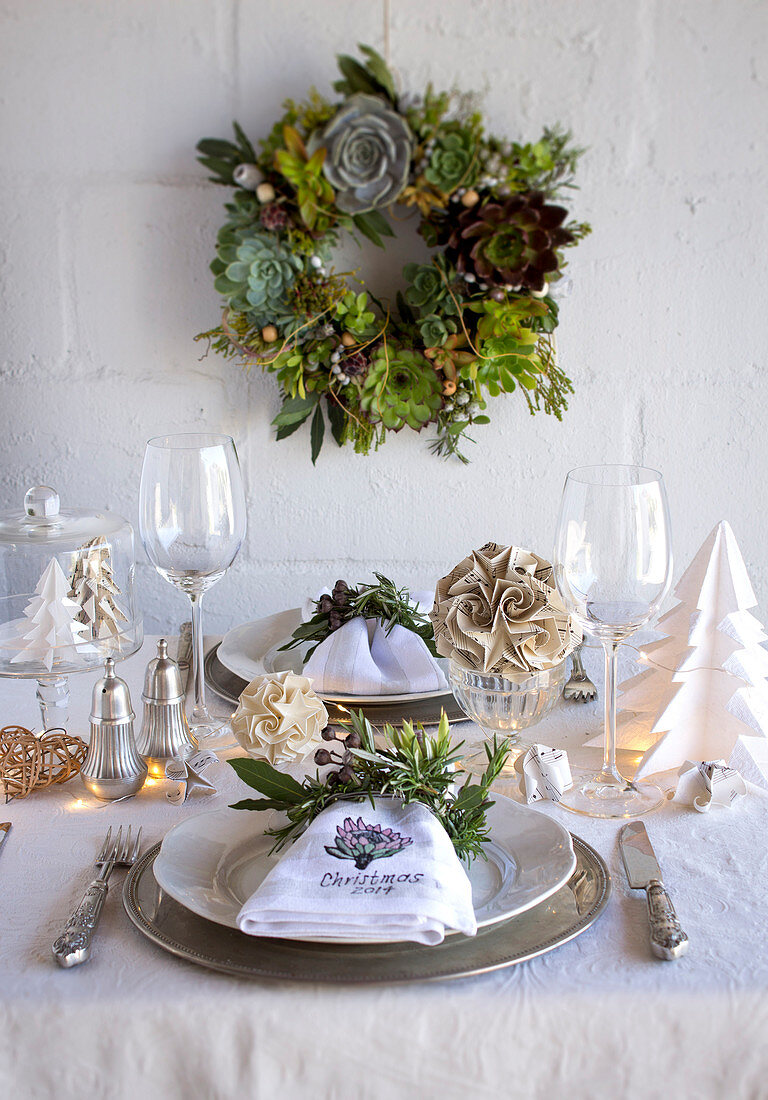 A wreath of succulents above a dining table decorated for Christmas