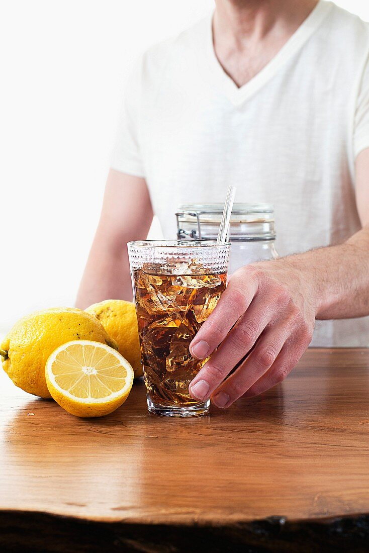 A man reaching for a glass of iced tea