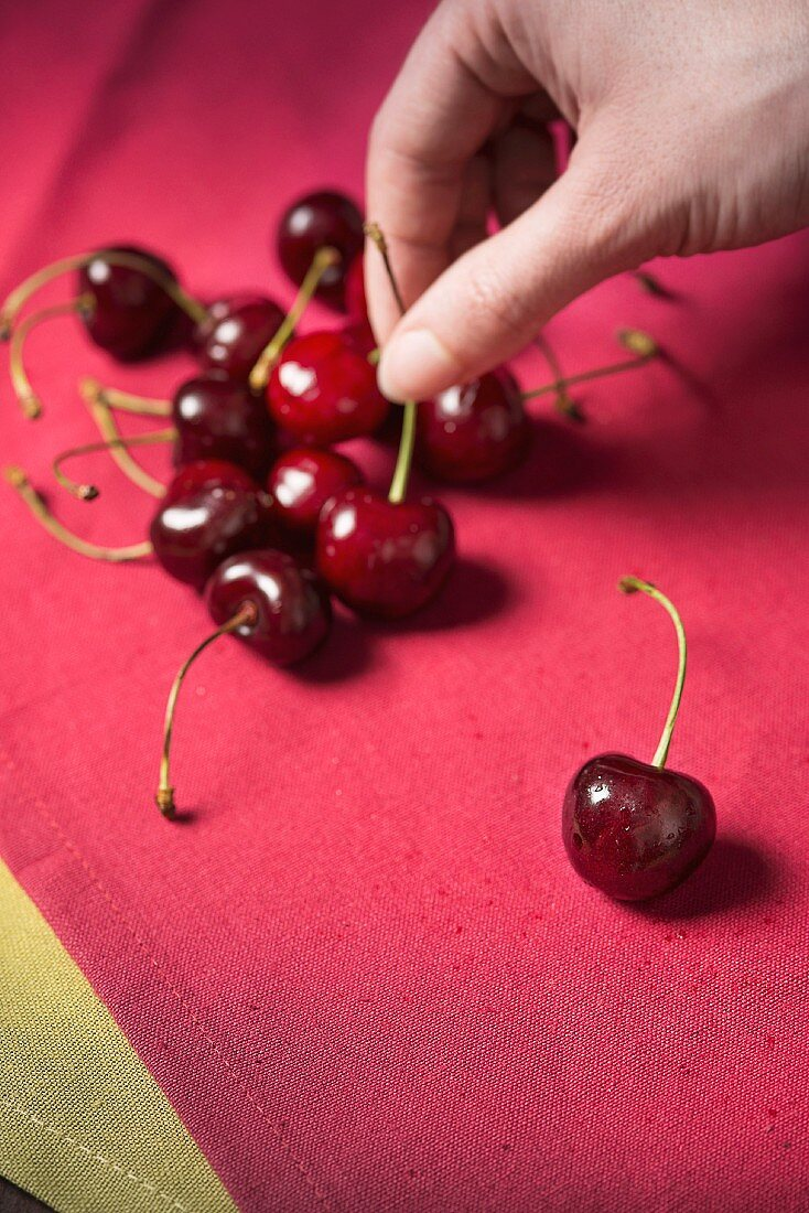 A hand reaching for cherries