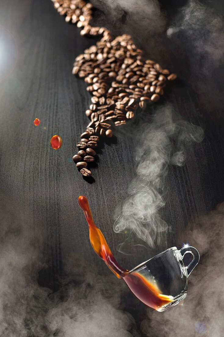 A steaming cup of coffee floating over a pile of coffee beans on a table