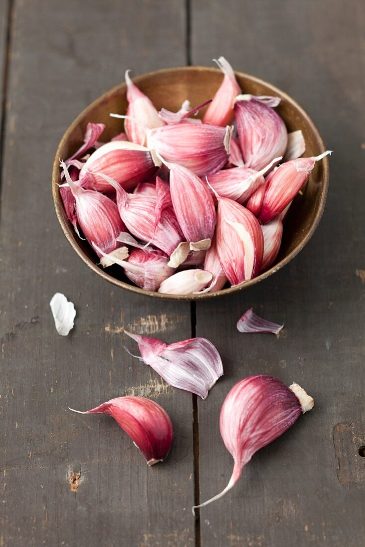 Garlic cloves in a small metal bowl