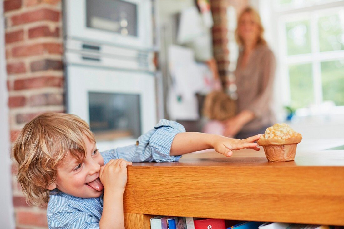 A little boy trying to reach a muffin on a kitchen counter