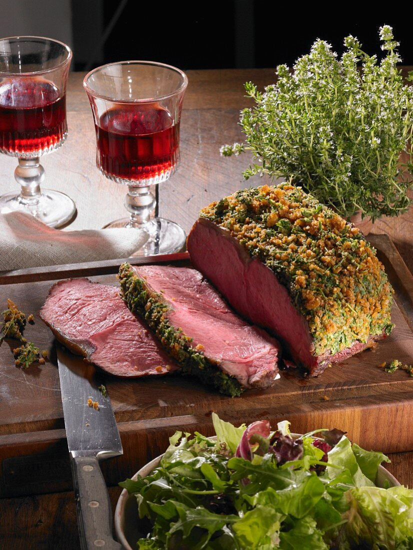 Sliced roast beef with a herb crust on a wooden board