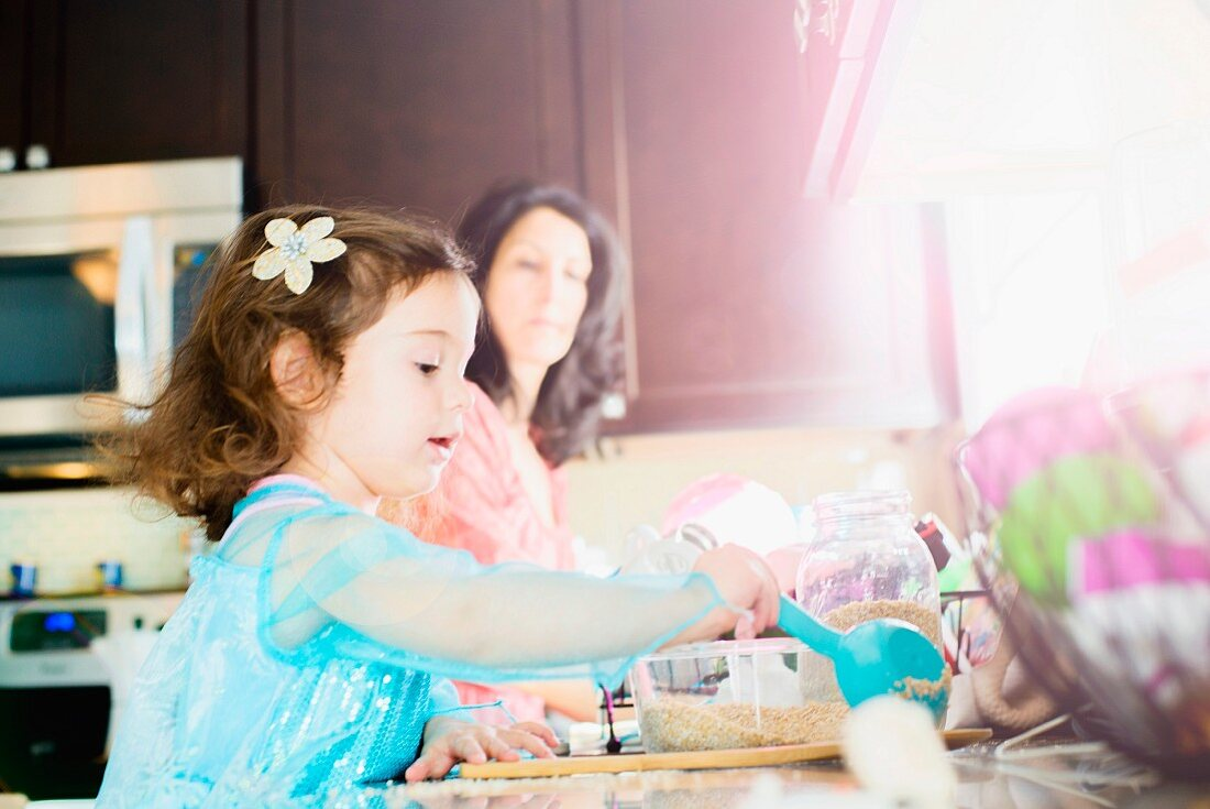 A little girl and her mother baking in a kitchen