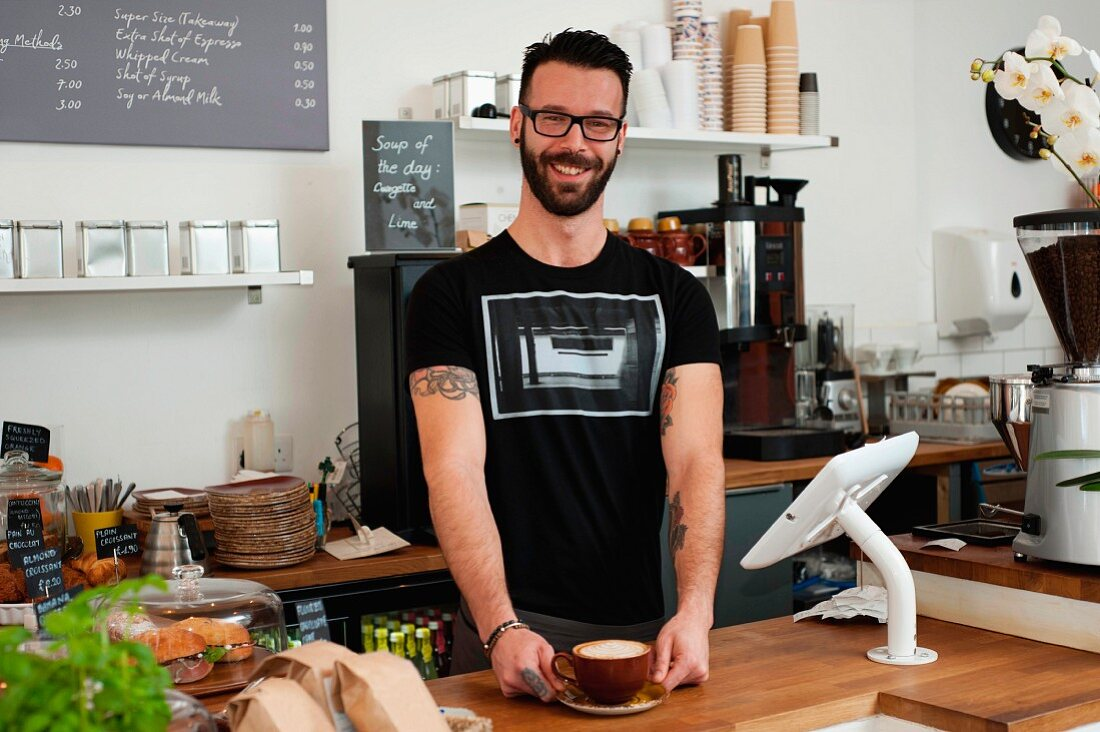 A young man holding a cup of coffee standing behind the sales counter in a cafe