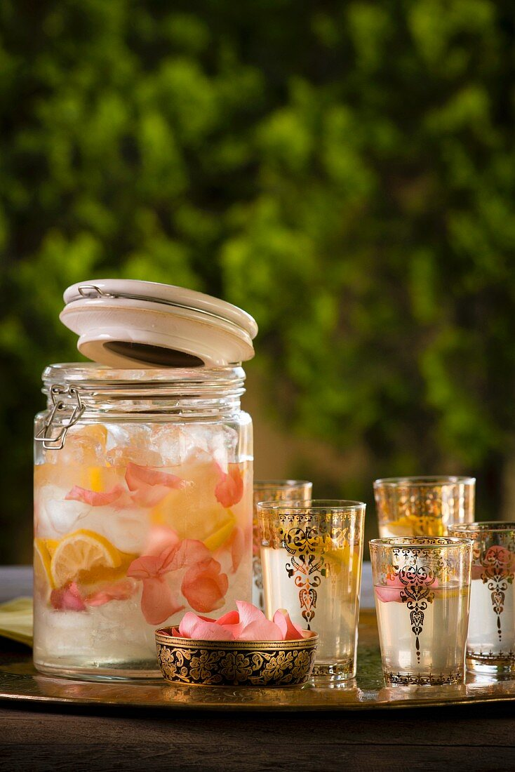 A jar of rose water lemonade and oriental tea glasses on a tray