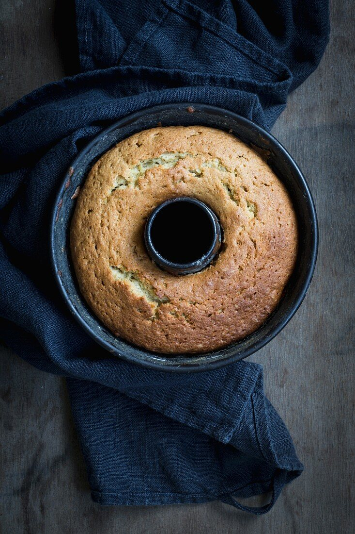 A freshly baked Bundt cake in a baking tin on a dark wooden surface with a grey cloth