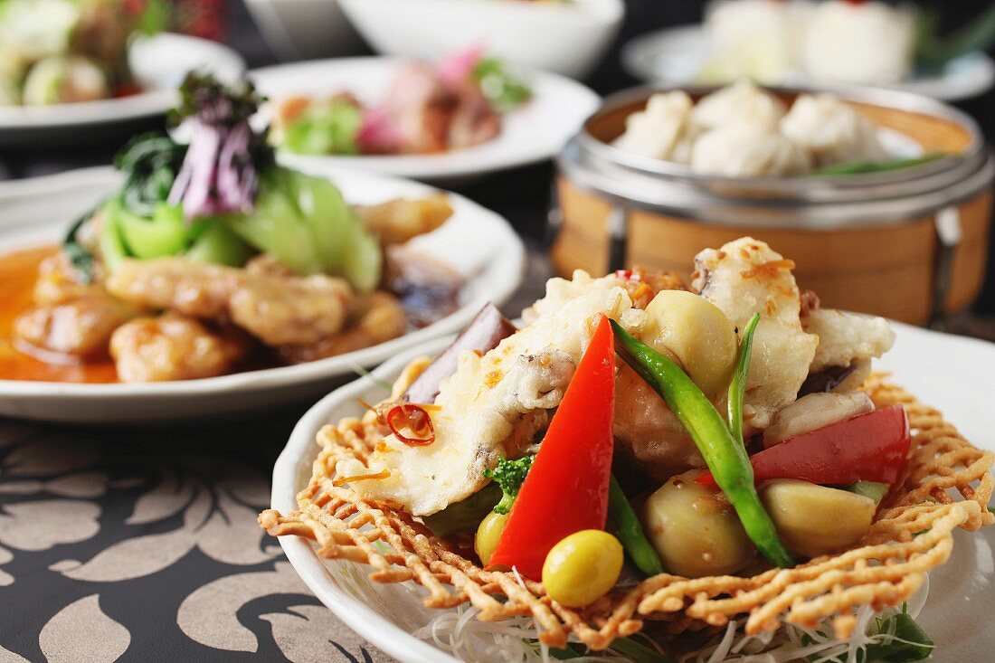 Grilled chicken with vegetables, and pork with vegetables and wontons in the background