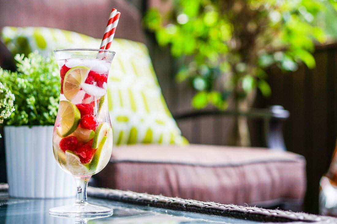 Fruity iced tea in a long drink glass with straws on a garden table